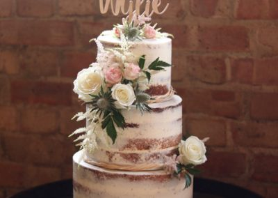 Semi naked wedding cake with bespoke topper
